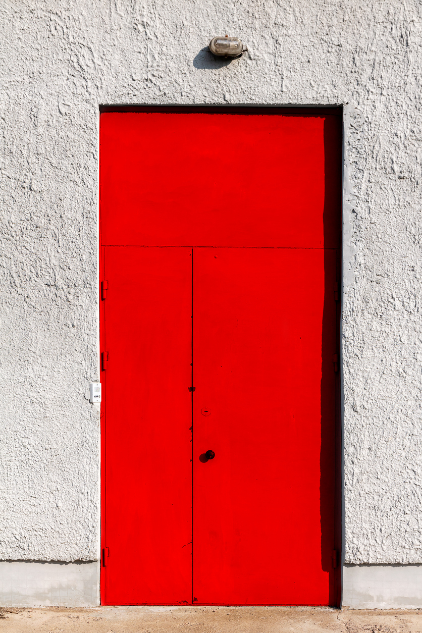 Red metal door in a concrete wall