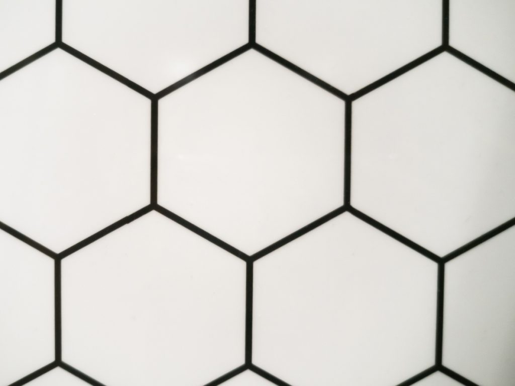 biele keramické obkladačky s čiernou škárovacou hmotou