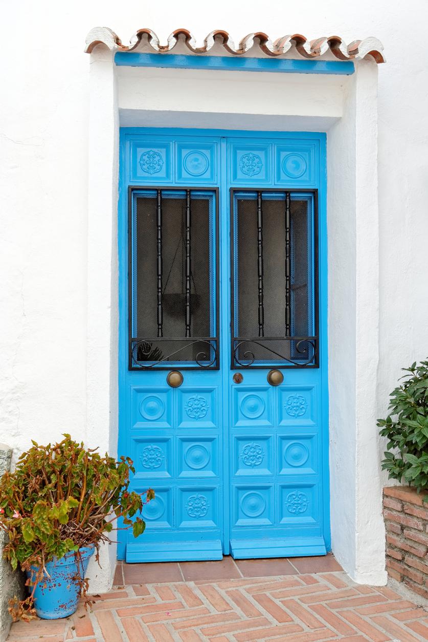 Blue wooden front door in s Spanish white village.