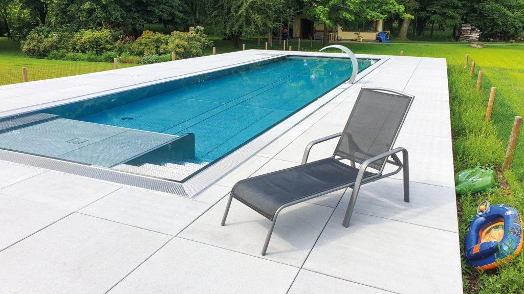Biela dlažba okolo bazéna s lehátkom