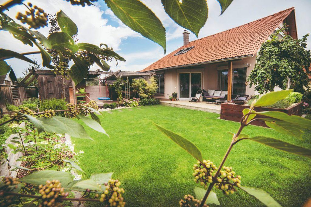 Útulná oddychová záhrada s množstvom rastlín, s pecou a so sedením pod pergolou