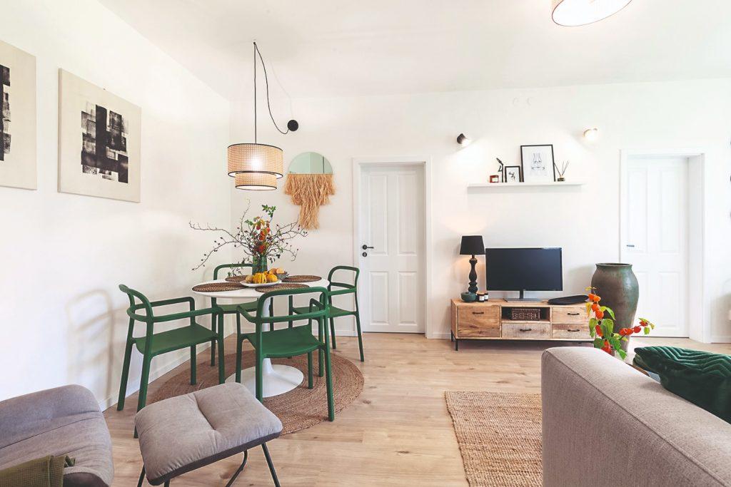Obývačka s jedálňou, drevenou komodou s televízorom a sivou pohovkou