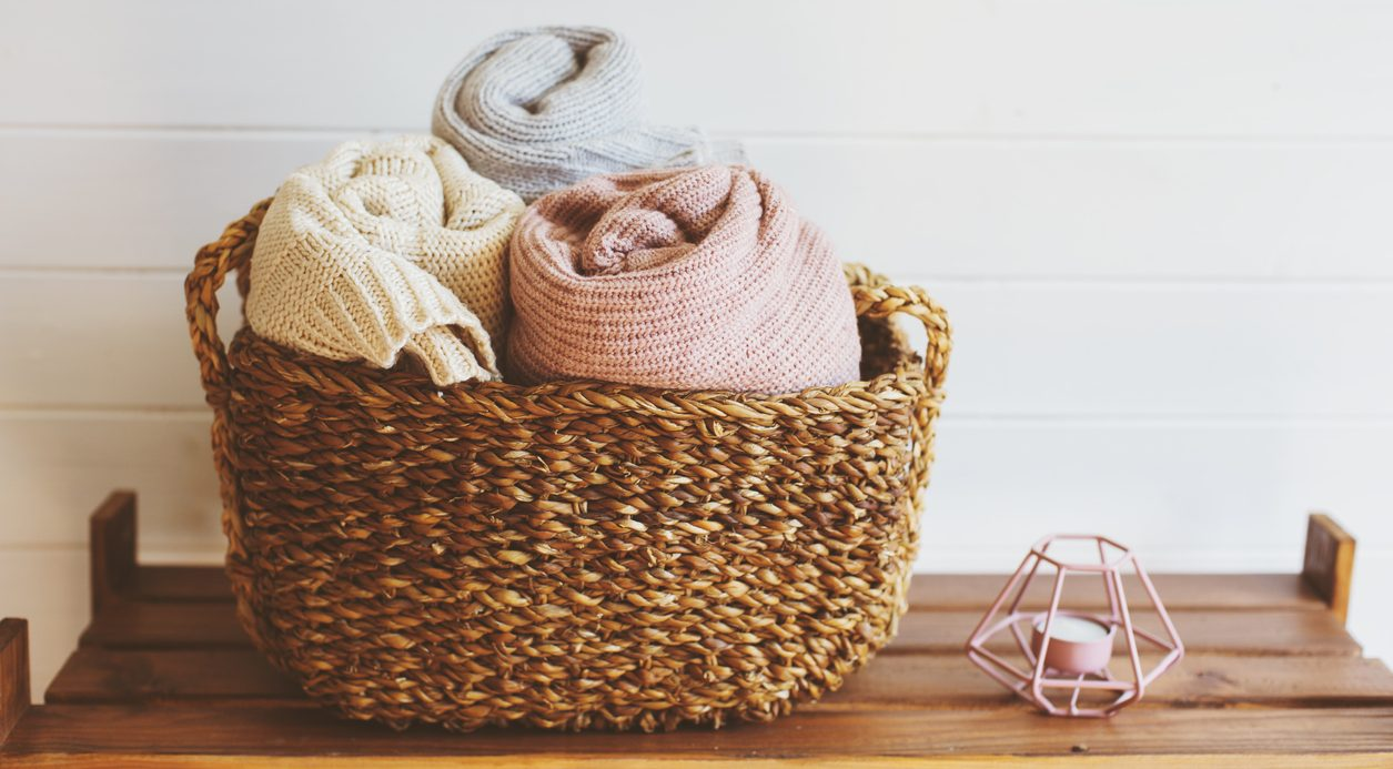 Cozy interior details, scandinavian mininalistic lifestyle. Organizing clothes in wicker backets, seasonal wardrobe and house cleaning, ideas for winter season.