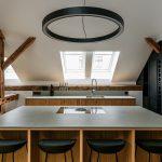 kuchyňa v podkroví s drevenými trámami a čiernou stenou