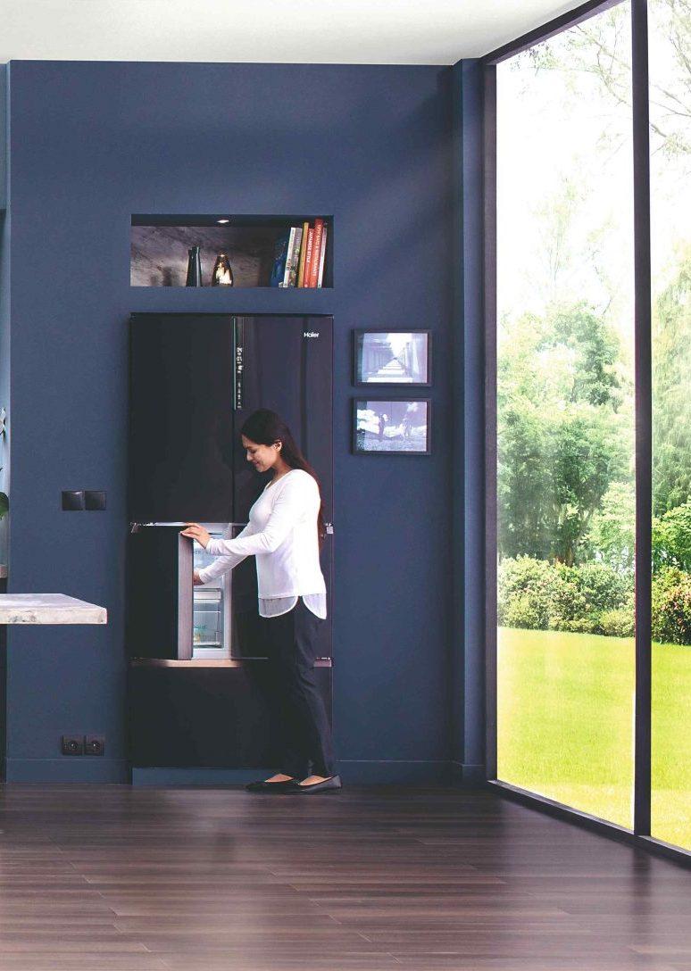 Žena otvára dizajnovú tmavú chladničku