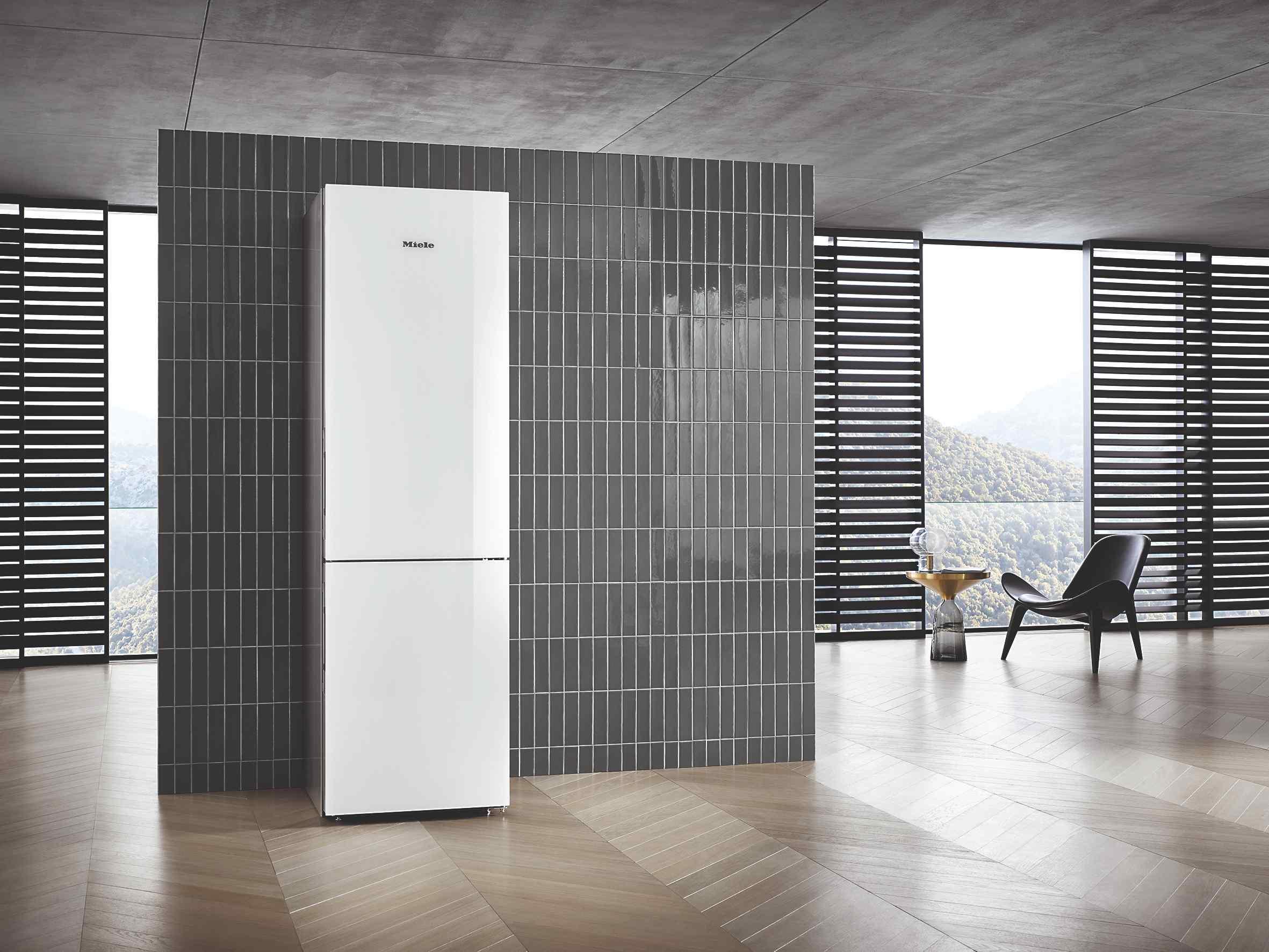 Voľne stojaca biela chladnička, sivý interiér s kachličkami
