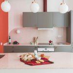 Sivá kuchyňa s červenou stenou raňajky na linke