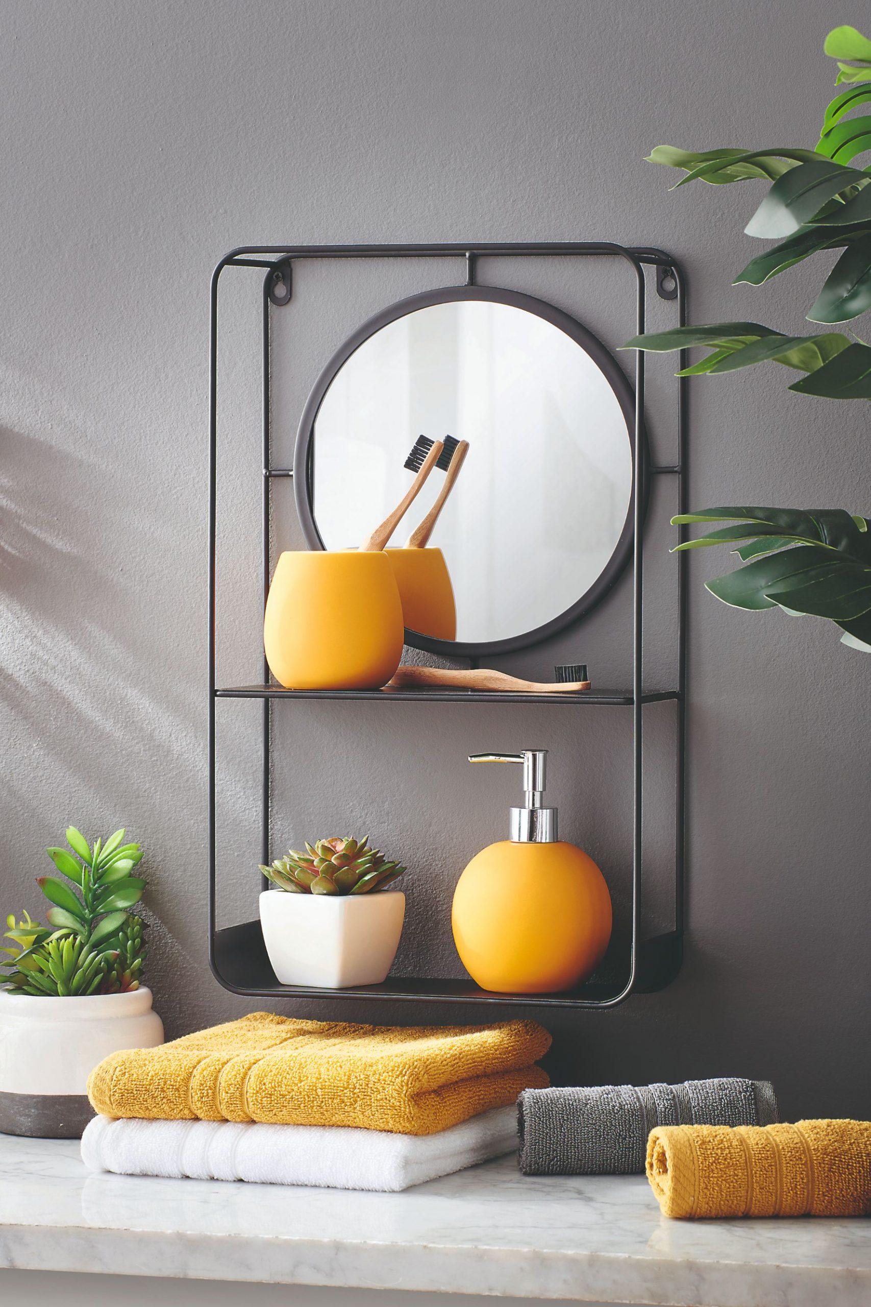 Žlté doplnky v kúpeľni s okrúhlym zrkadlom