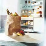 Papierová taška s nákupom pred otvorenou chladničkou