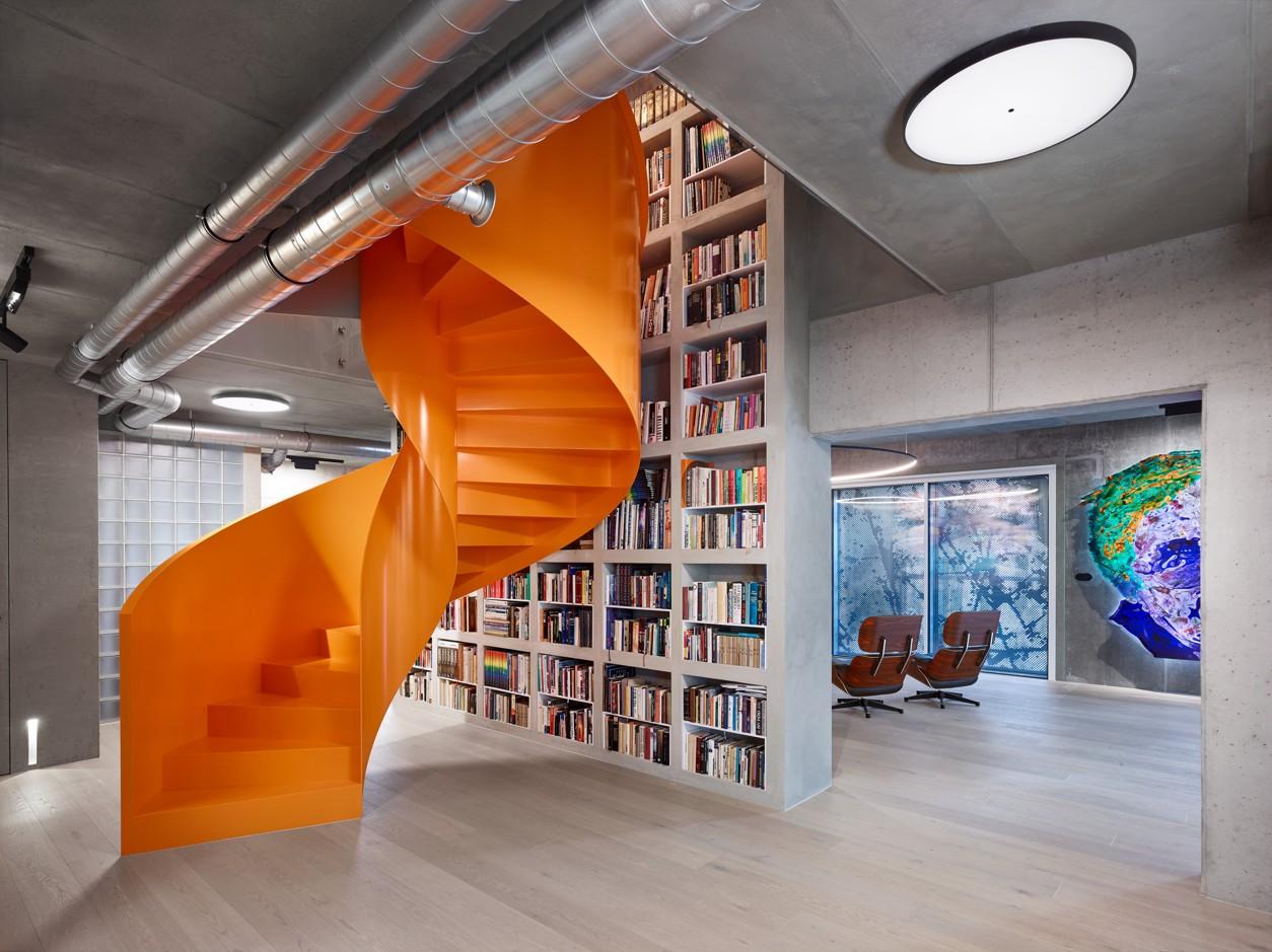 Oranžové točité schody s veľkou knižnicou