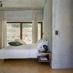 Bledá spálňa betónové steny a závesy