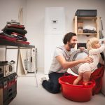 Otec s dieťaťom pri otvorenej práčke v technickej miestnosti