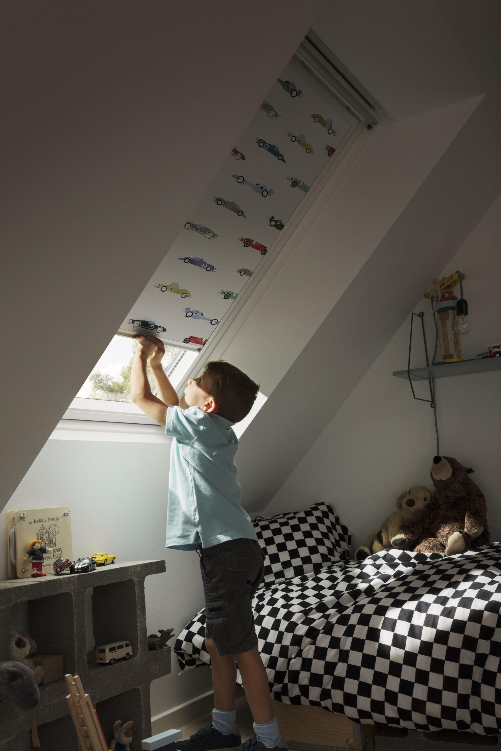 Chlapec sťahuje vzorované rolety v detskej