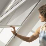 Žena zaťahuje tienenie na strešnom okne