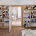 Police z dreva na jednej stene s knihami