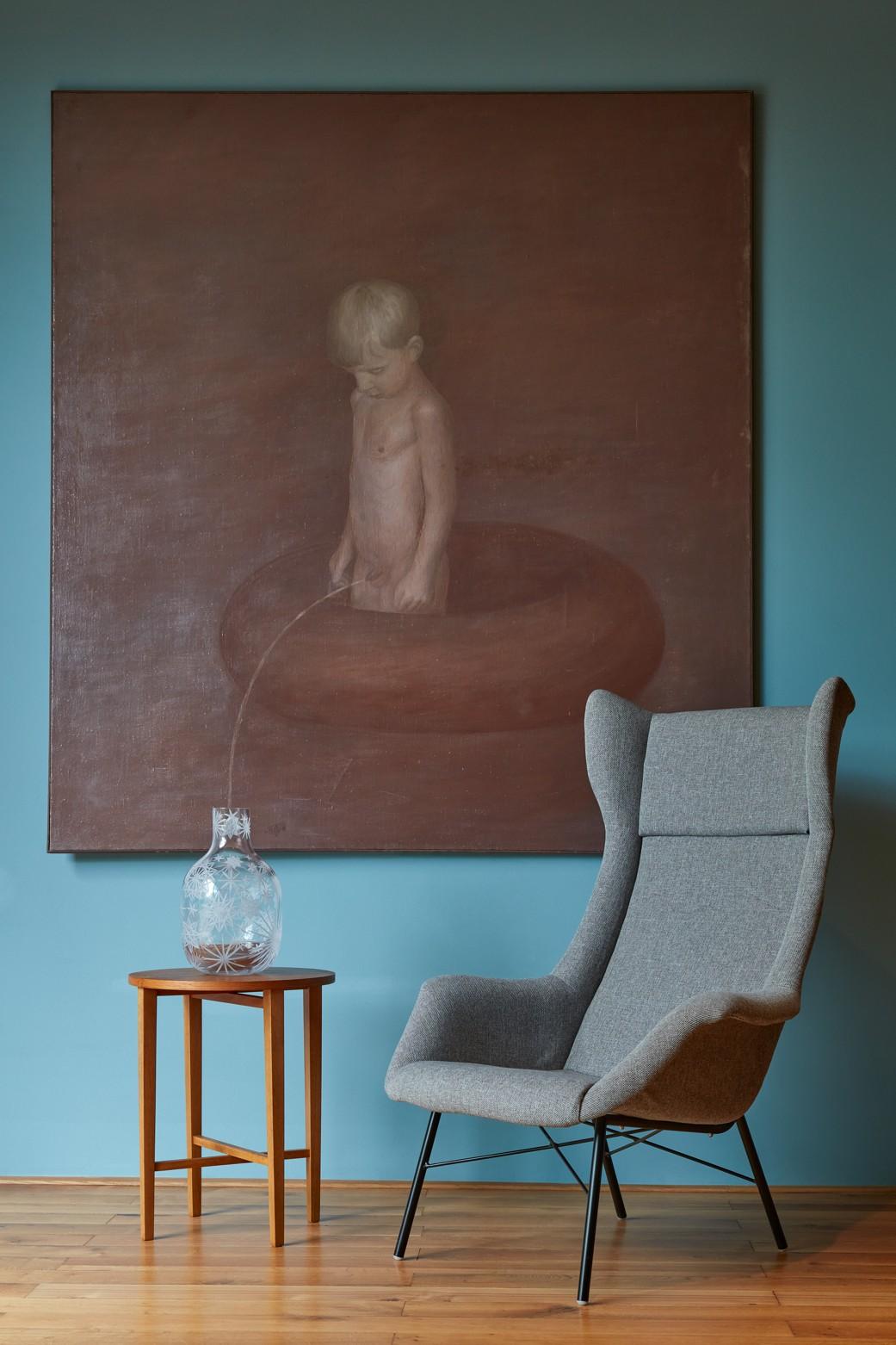 Obraz cikajúceho chlapca do vázy na stolíku