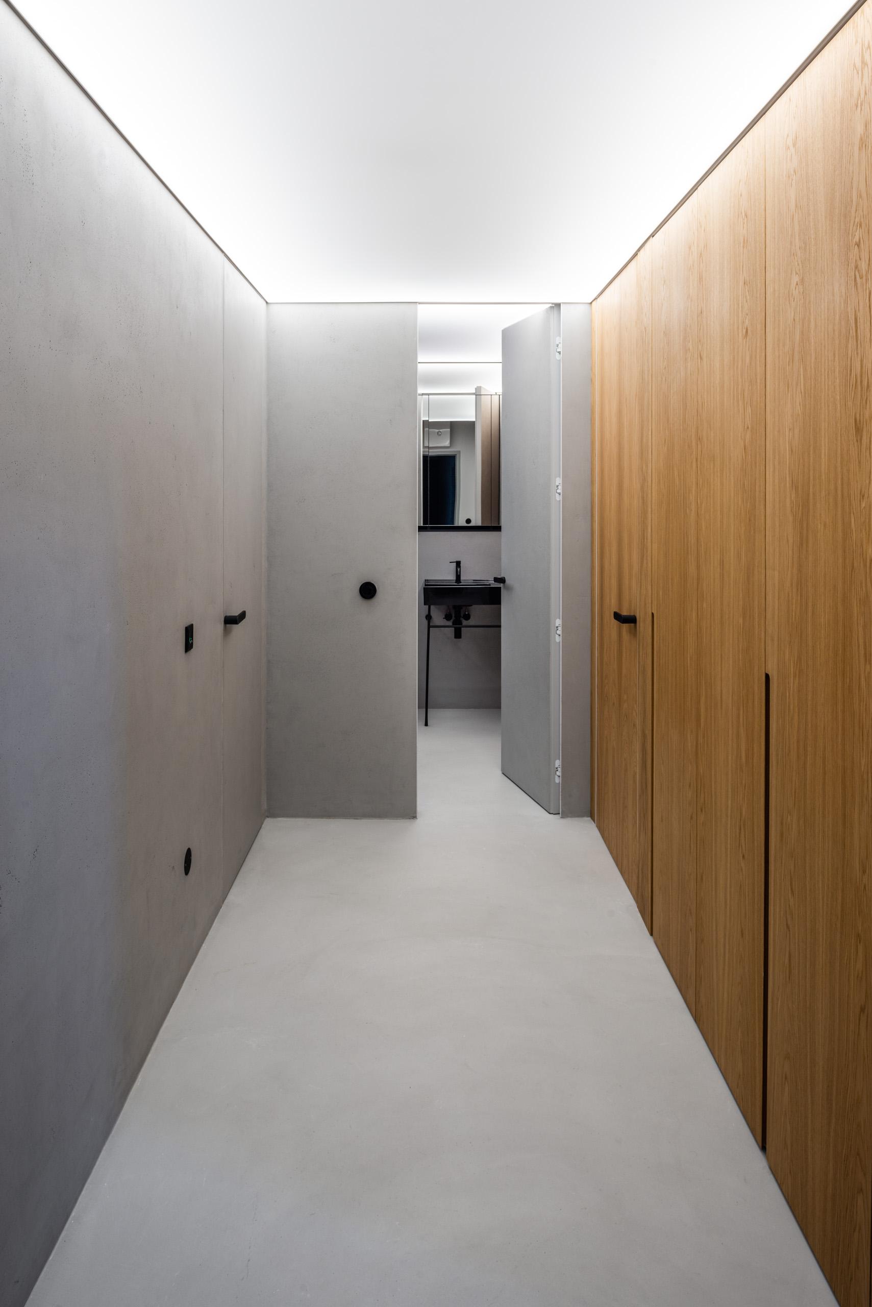 Chodba so sivými stenami a dubovým vstavaným nábytkom