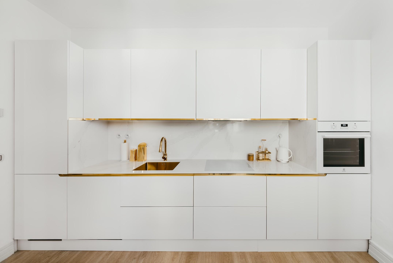 Kuchyňa s bielou linkou a mosadzné detaily