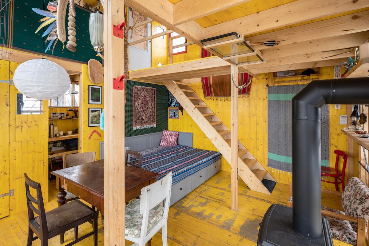 Chatka so žltým interiérom, schodmi a pohovkou