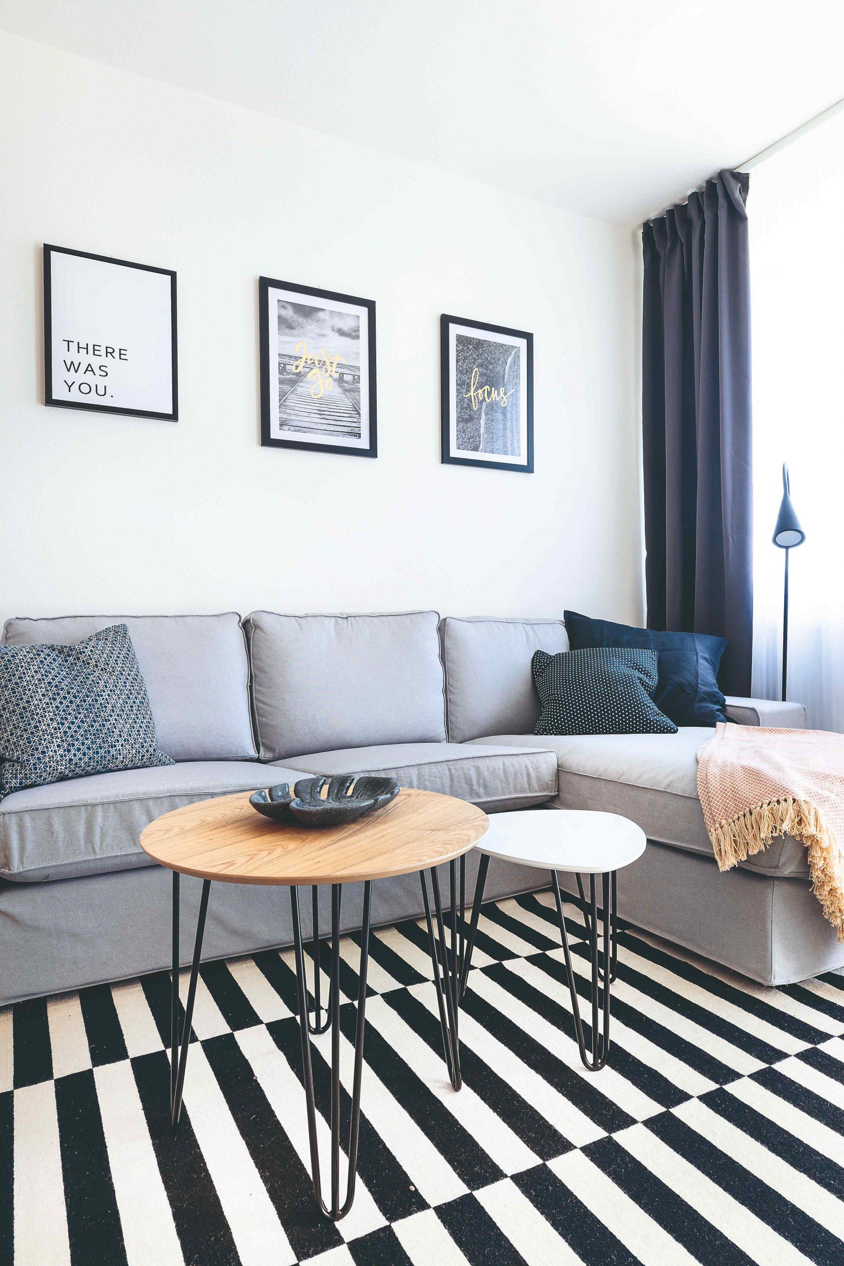 Obývacia izba s veľkou sivou sedačkou a obrazmi