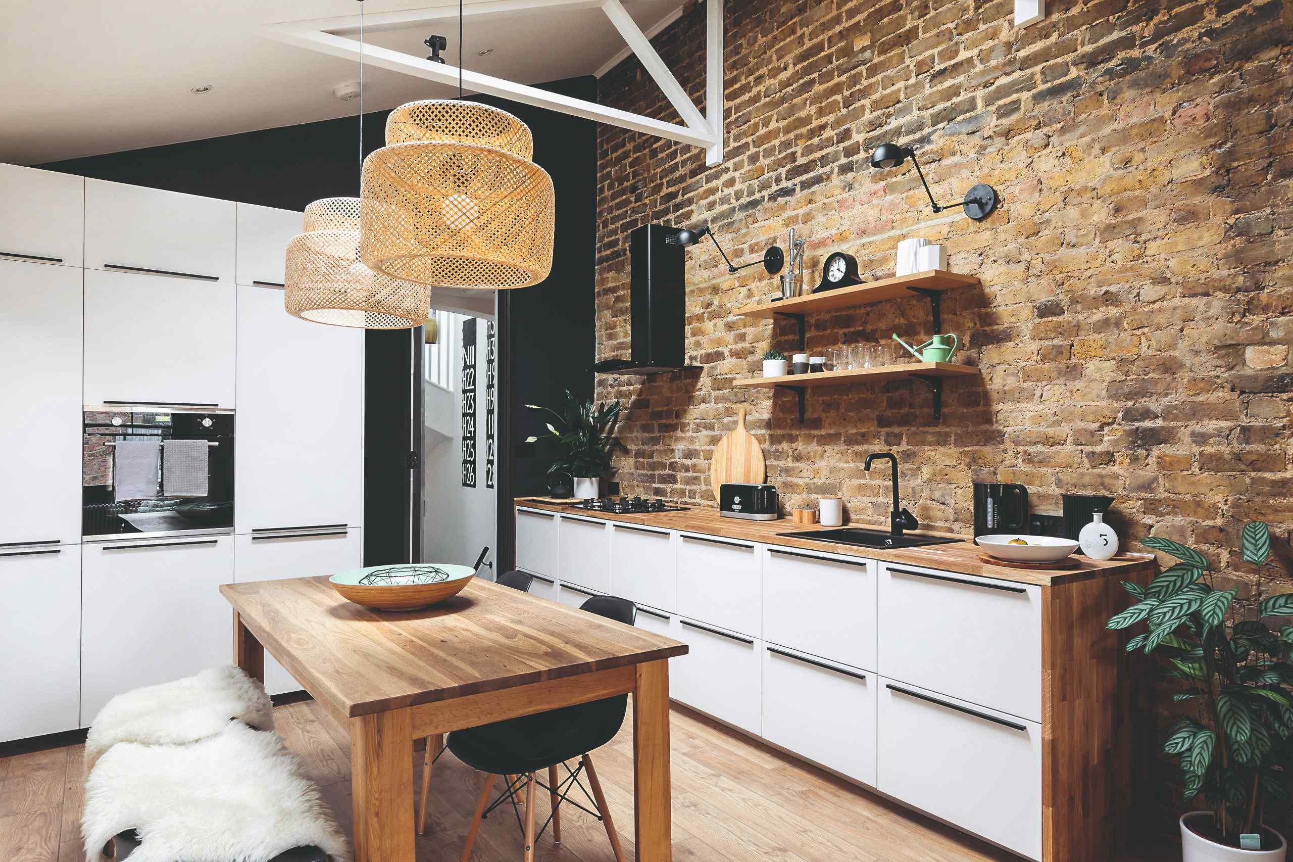 Kuchyňa s dreveným stolom a tehlovou stenou