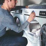Muž nastavuje sušičku prádla