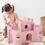 Ružový hrad z krabice a hrajúce sa dievčatko