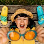 Žena usmiata s okuliarmi v rukách