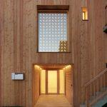 Vyrezávaná drevená mozaika nad vchodom do modernej stodoly