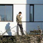 Muž stojí na terase domu