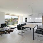 Biela lesklá kuchyňa a obývačka s koženými kreslami