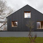 Robustná čierna fasáda so svetlými oknami