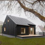 Čierny dom s terasou a svetlými oknami