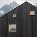 Robustná čierna fasáda s nepravidelnými oknami