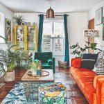 Obývačka plná obrazov, farebná sedačka a vankúše