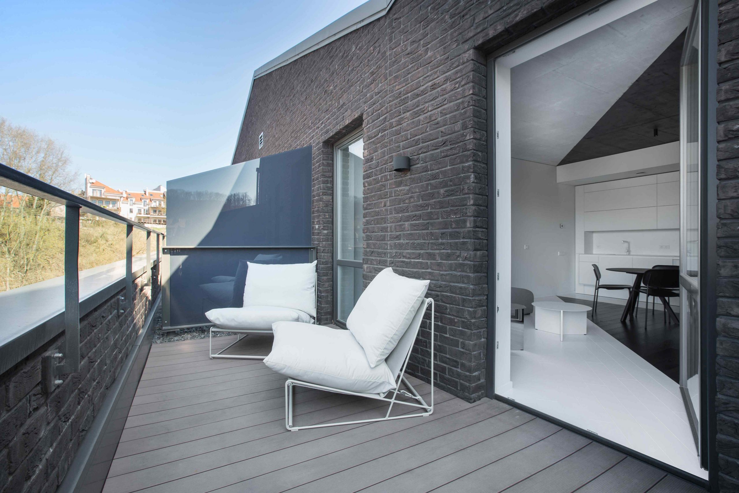 Priestranná terasa bytu s dvoma bielymi kreslami