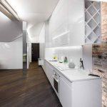 Biela kuchyňa pozdĺž steny a tmavá drevená podlaha