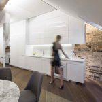 Lesklá biela kuchyňa a tehlová stena