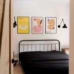 Spálňa s čiernou posteľou a grafiky