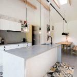 Biela kuchyňa s betónovou dlažbou a trámami