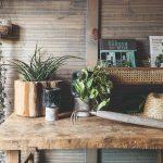 Starý drevený stôl s kvetináčmi, náradím a klobúkom