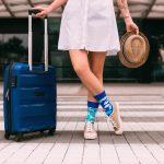 Žena v modrých ponožkách a sukni čakajúca s kufrom