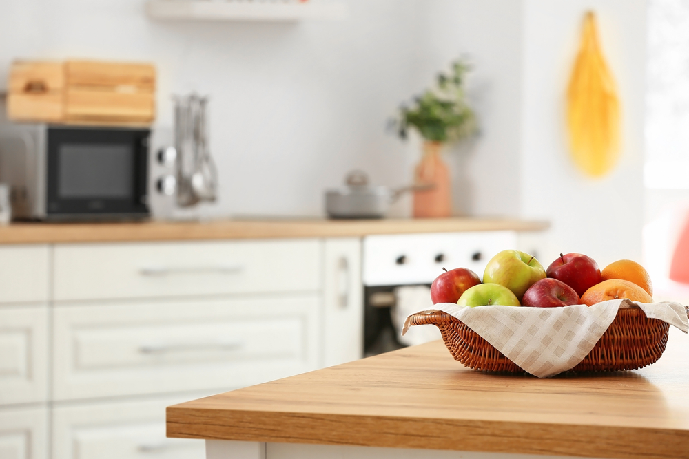 biela kuchyňa s drevenou pracovnou doskou