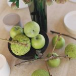 Jablká na stole s vázou kvetov