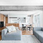 Obývačka se šedou pohovkou a betónovým pilierom