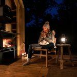Žena s čajom pri krbe v otvorenej chate