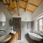 Moderná sivá kúpeľňa s trámami a oblými tvarmi