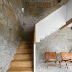 Drevené schody s vonkajšej strany biele v kamennom interiéri