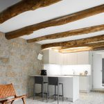 Biela rohová kuchyňa v kamennom interiéri