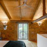 Spálňa s dreveným stropom a kamennou stenou